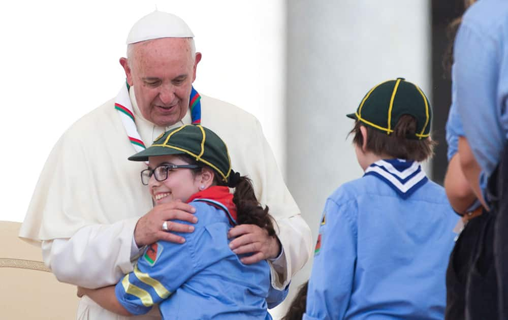 Pope Francis hugs a girl at the end of an audience with Italian AGESCI boy scouts association's members in St. Peter's Square at the Vatican.