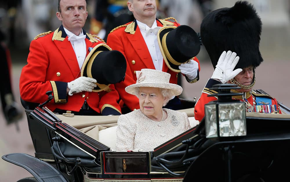 Britain's Queen Elizabeth II and Prince Philip ride in a carriage during the Trooping The Colour parade at Buckingham Palace, in London.