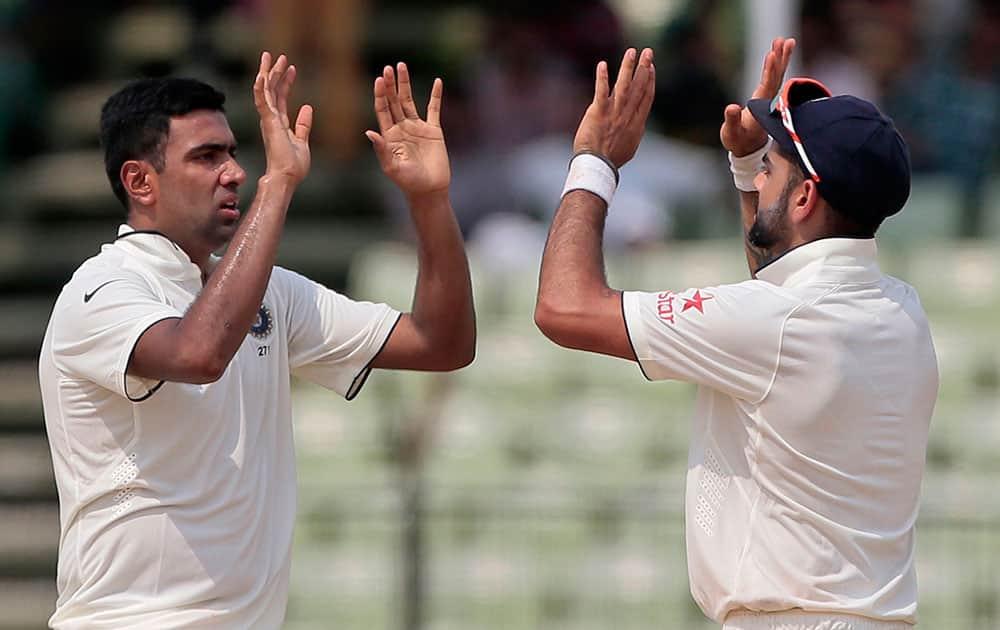India's Ravichandran Ashwin, left, celebrates with captain Virat Kohli after the dismissal of Bangladesh's Shuvagata Hom on the last day of the test cricket match between them in Fatullah, Bangladesh.