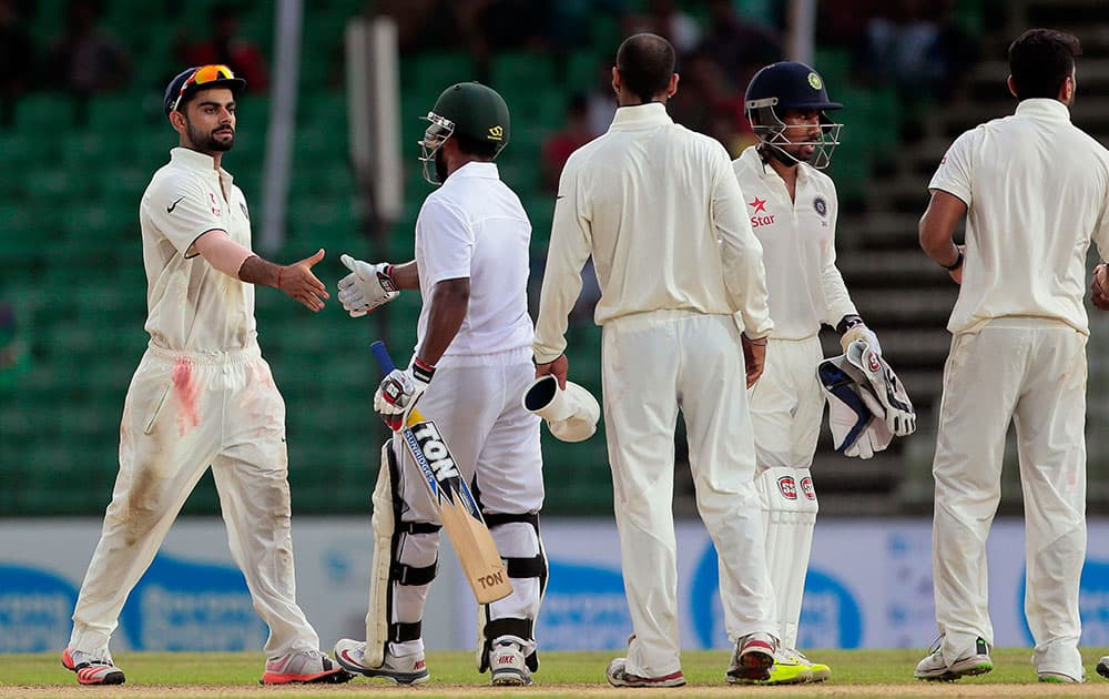 India's captain Virat Kohli, left, shakes hand with Bangladesh's Imrul Kayes, second left, at the end of the final day of their cricket test match in Fatullah, Bangladesh.
