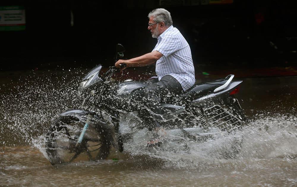 A  man rides a bike through a water-logged street as it rains in Mumbai, India.