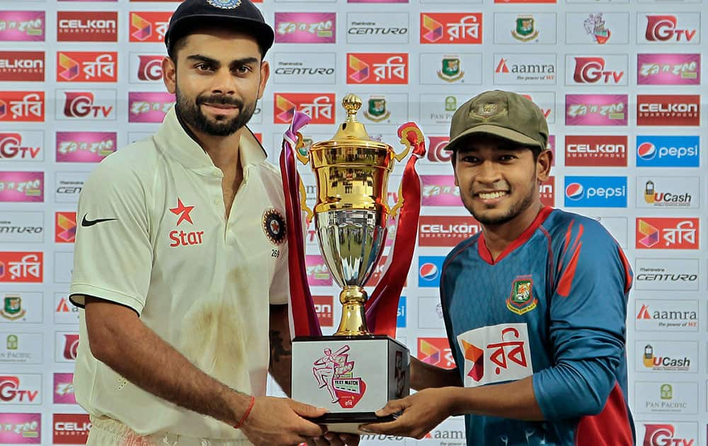 INDIA'S CAPTAIN VIRAT KOHLI AND BANGLADESH'S CAPTAIN MUSHFIQUR RAHIM POSE FOR PHOTOGRAPHS WITH THE WINNERS TROPHY AT THE END OF THE FINAL DAY OF THE CRICKET TEST MATCH AGAINST BANGLADESH IN FATULLAH, BANGLADESH.