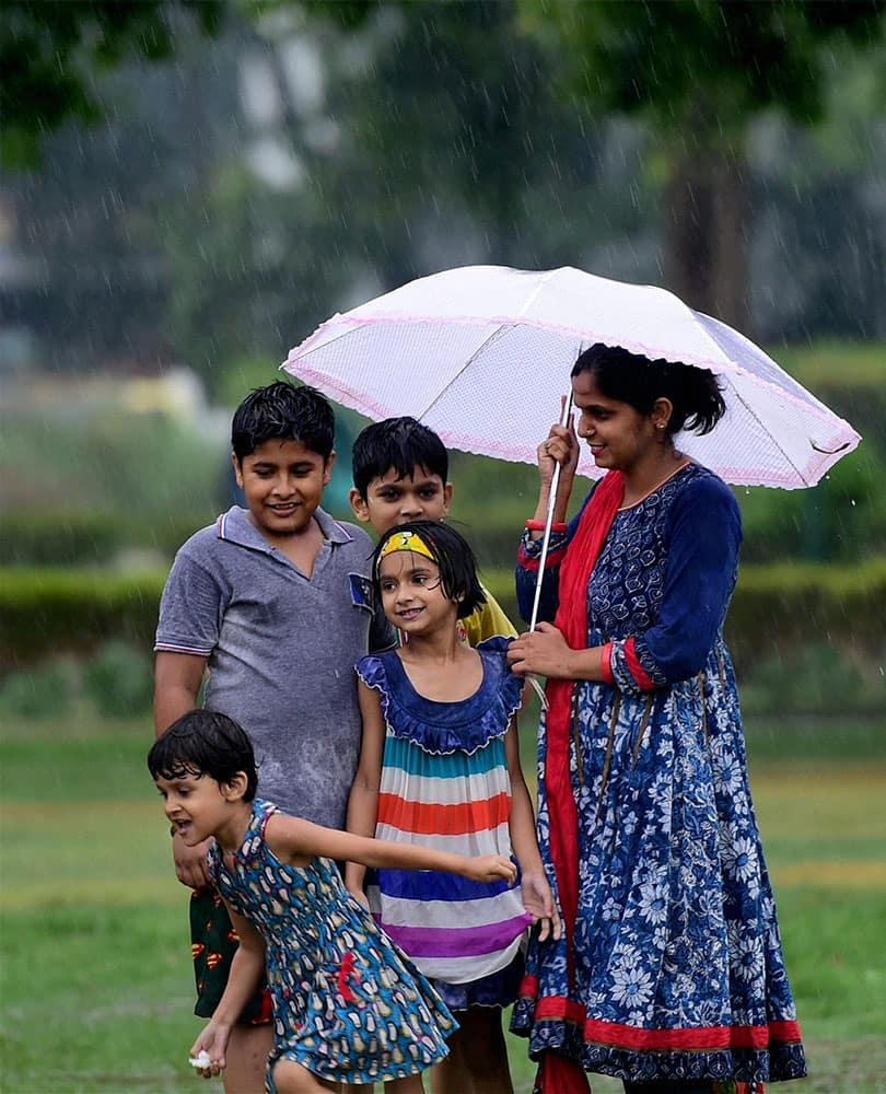 Children enjoy monsoon shower in New Delhi.