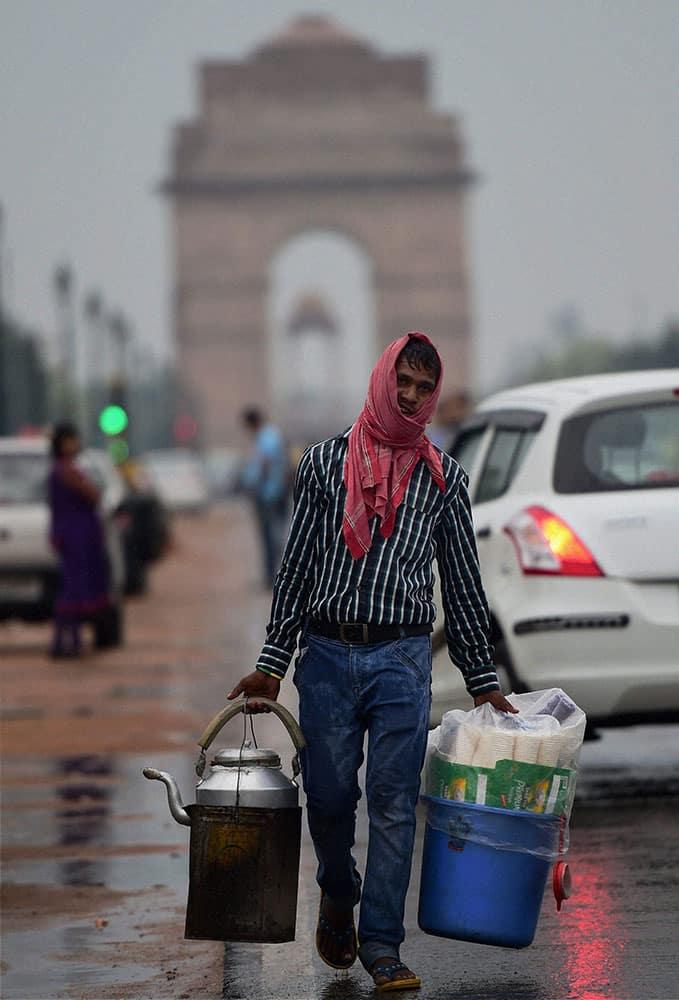 A tea vendor walks along Rajpath after rains in New Delhi.