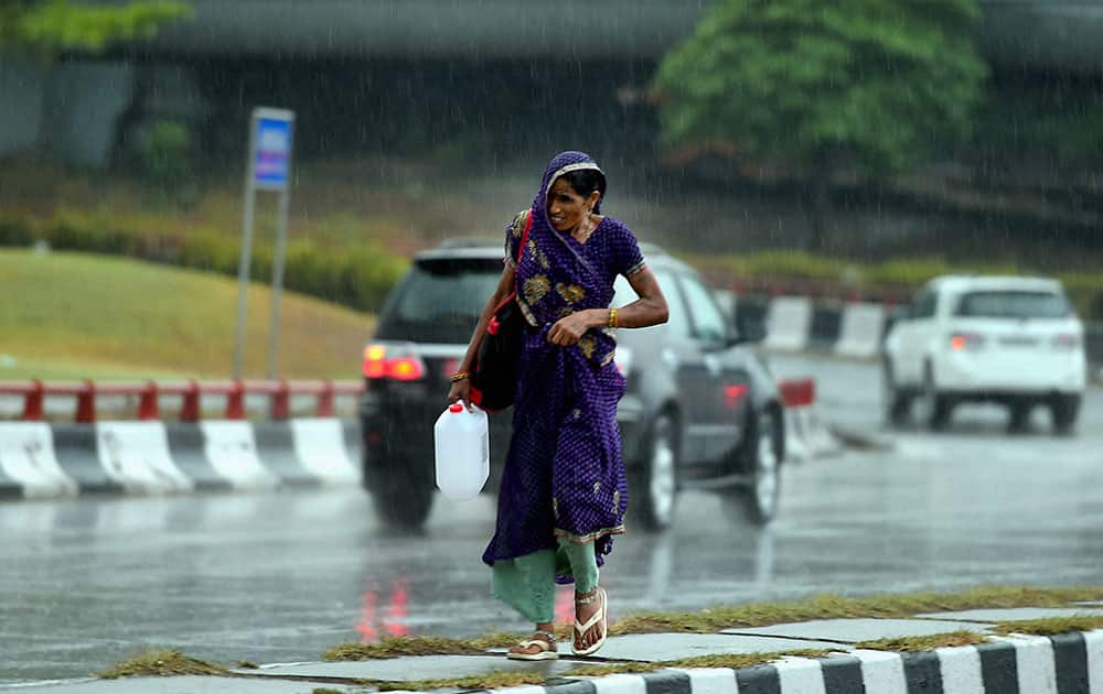 A woman walks cautiously at a road divider as it rains at India Gate in New Delhi.