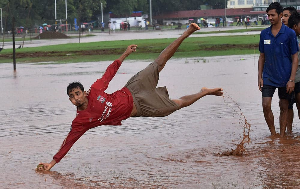 Boys play in the rain water at Azad Maidan in Mumbai.
