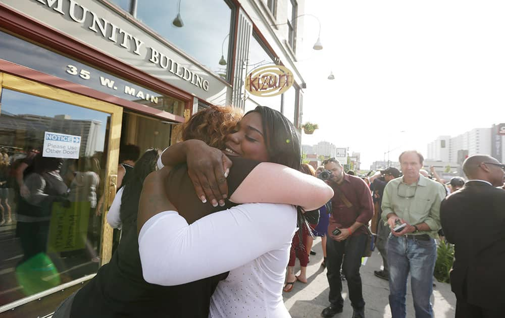 Kitara Johnson, right, and Heidi Peterson hug after a demonstration for local NAACP chapter president Rachel Dolezal to step down, in Spokane, Wash.