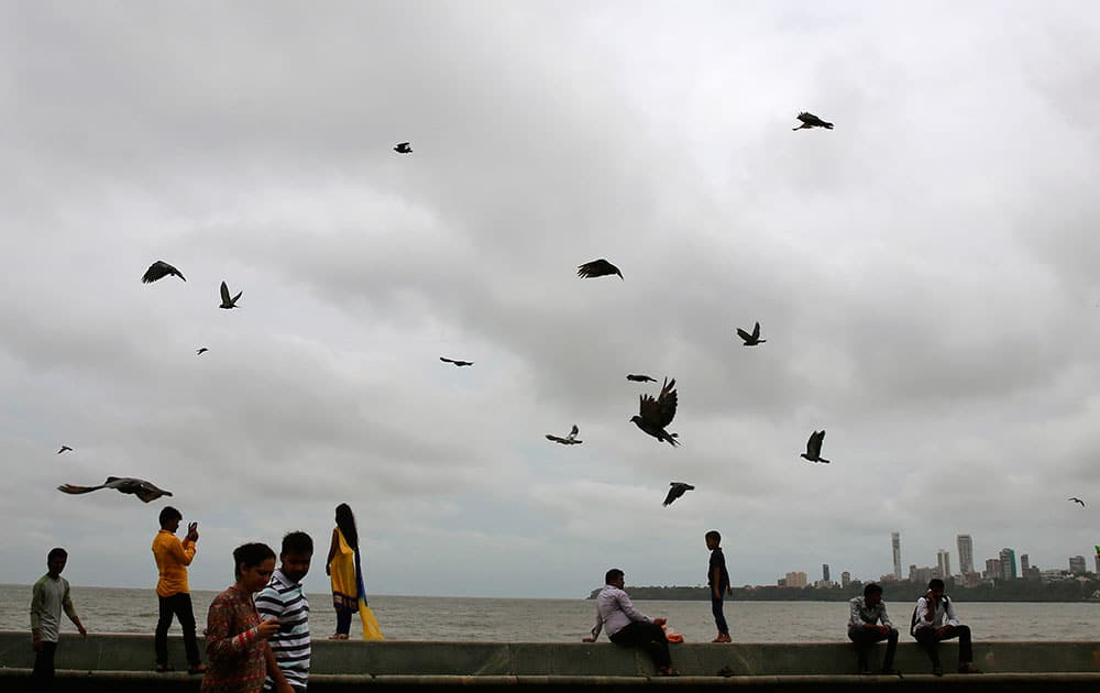 Indians sit on the promenade as others walk through the Arabian Sea coast during the monsoon season in Mumbai.