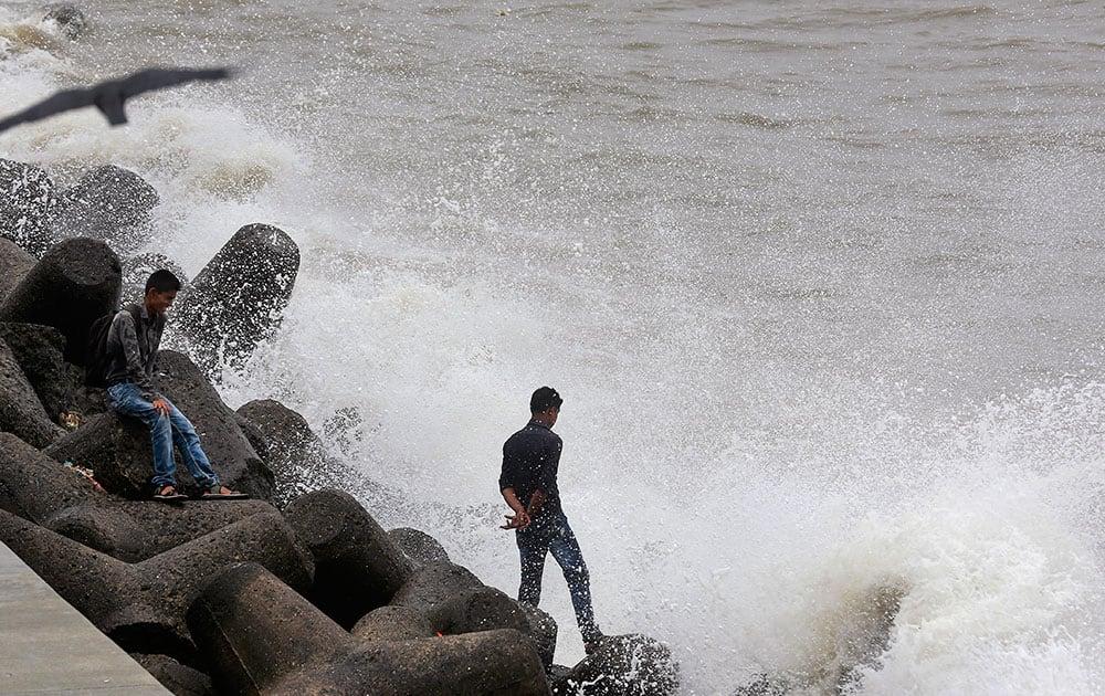 Indians enjoy high tide waves on the Arabian Sea coast in Mumbai.