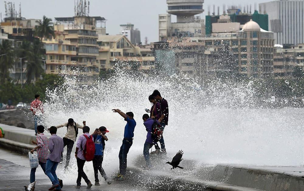 Mumbaikars enjoy high tide during a monsoon season in Mumbai.