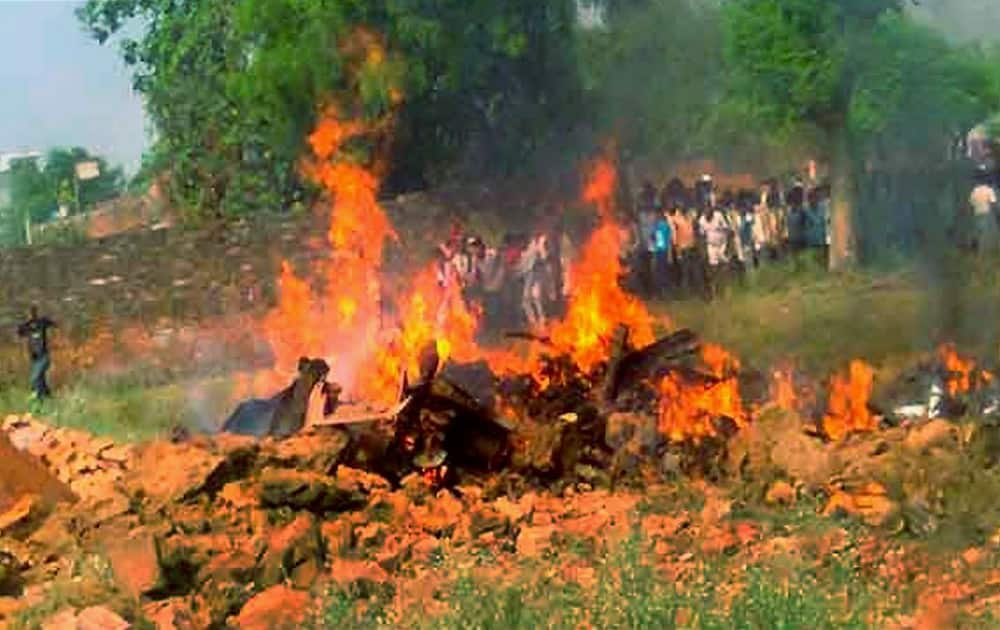 People gather near thet spot after a Jaguar fighter plane crashed at Chaka village near Karchana in Allahabad.