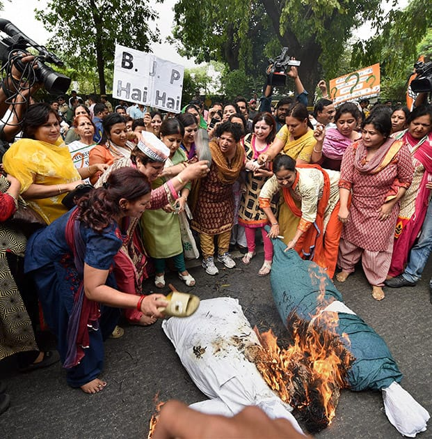Mahila Congress workers burning effigies of Prime Minister Narendra Modi and Foreign Minister Sushma Sawraj during a protest at BJP office in New Delhi. Swaraj facilitated former Indian Premier League (IPL) chief Lalit Modi's travel to Portugal for his wife's treatment last year.