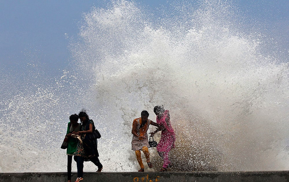girls enjoy high tide waves marking the arrival of monsoon season on the Arabian Sea coast in Mumbai.