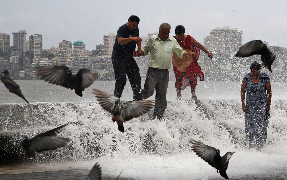 People try to walk away as huge tidal waves hit the Arabian Sea shore marking the arrival of monsoon season in Mumbai.