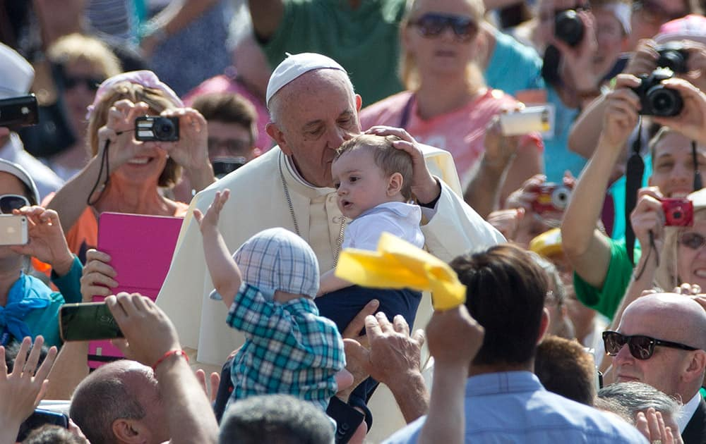 Pope Francis kisses a baby as he arrives for his weekly general audience, in St. Peter's Square at the Vatican.