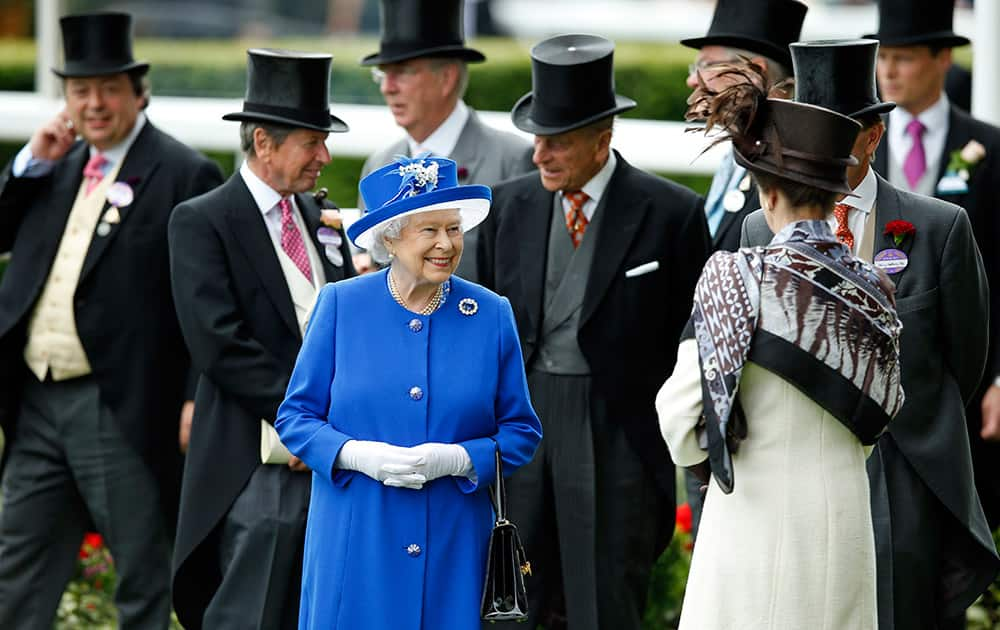 Britain's Queen Elizabeth II smiles as she walks in the paddock on the second day of Royal Ascot horse racing meet at Ascot, England.