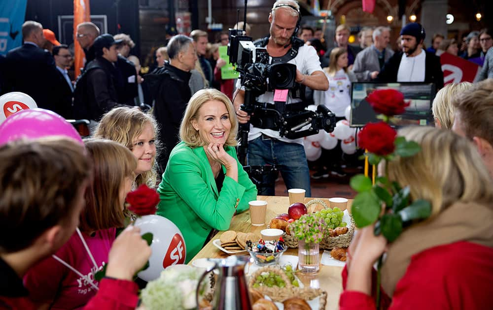 Danish Prime Minister and head of the Social Democrats Helle Thorning-Schmidt smiles as she has breakfast during a live TV show on the floor of the Central Station in Copenhagen, Denmark. Danes are voting Thursday in parliamentary elections that will determine whether the center-left government of Thorning-Schmidt can continue or whether the center-right opposition will be back at the helm.