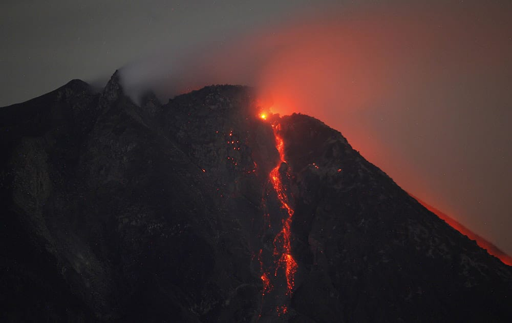 Hot lava flows from the crater of Mount Sinabung as seen from Tiga Pancur, North Sumatra, Indonesia.