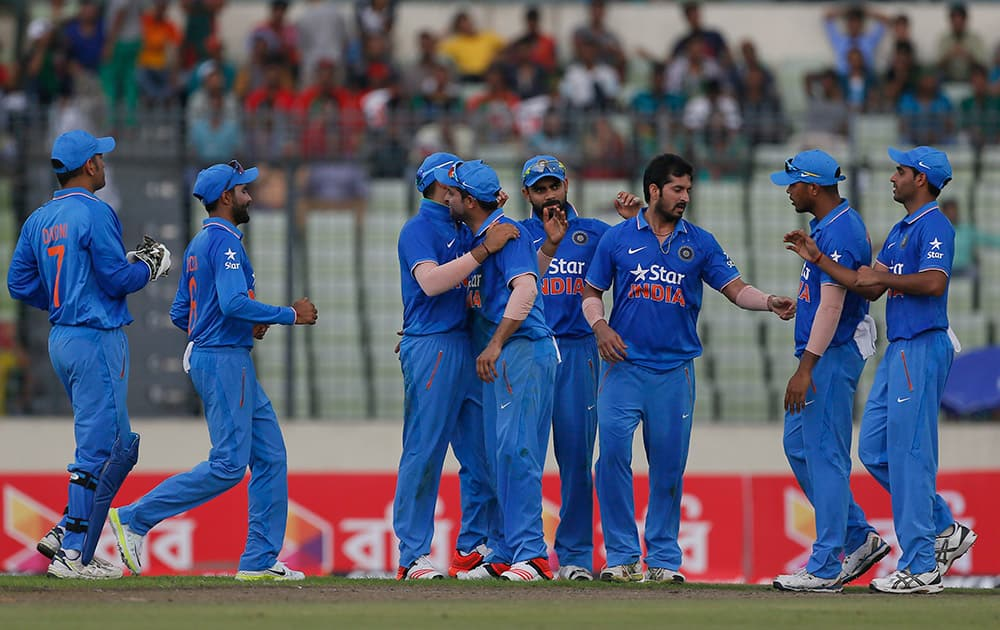 Teammates congratulate India's Suresh Raina, center, after the dismissal of Bangladesh's Soumya Sarkar during the first one-day international cricket match in Dhaka, Bangladesh.