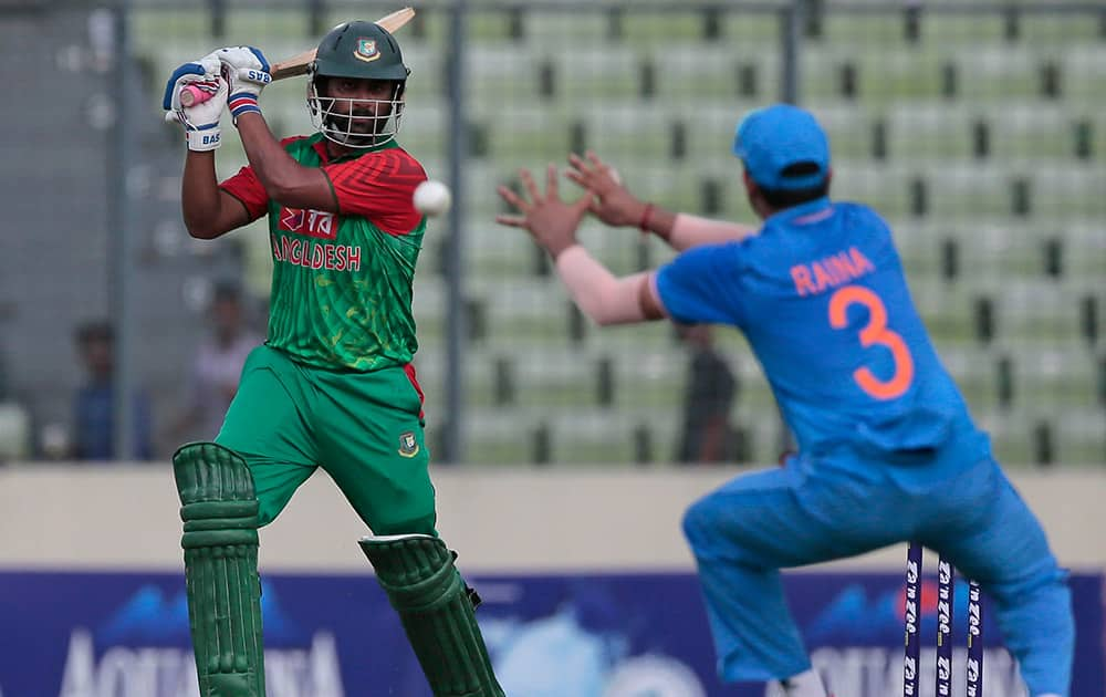 Bangladesh's Tamim Iqbal, plays a shot, as India's Suresh Raina attempts to field during their first one-day international cricket match in Dhaka, Bangladesh.