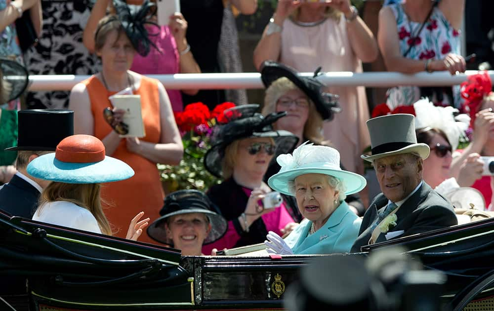 Britain's Queen Elizabeth II, with Prince Philip arrive in the parade ring on the third day of the Royal Ascot horse racing meet at Ascot, England.