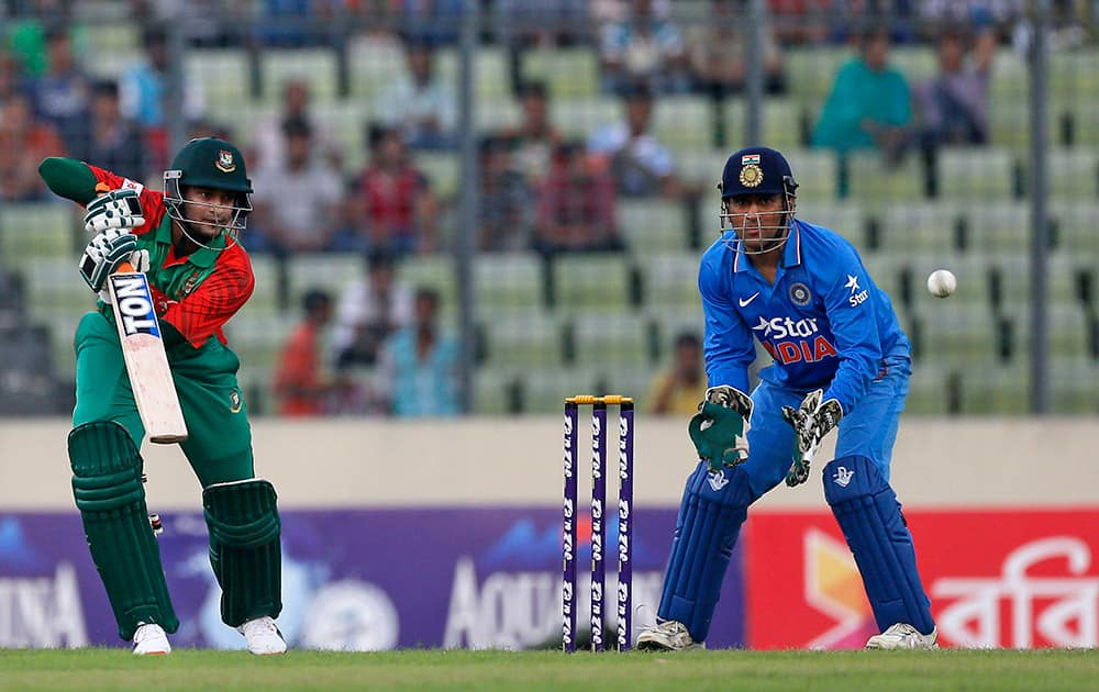 Shakib Al Hasan plays a shot as wicketkeeper MS Dhoni watches during the first one-day international cricket match between them in Dhaka, Bangladesh.