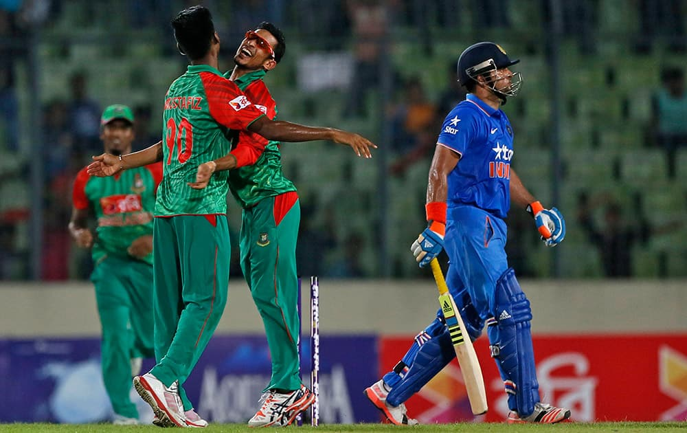 Bangladesh's Mustafizur Rahman, left, celebrates with teammate Nasir Hossain, center, the dismissal of India's Suresh Raina, right, during the first one-day international cricket match between them in Dhaka.