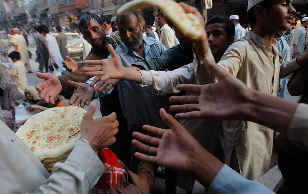 A Pakistani man distributes bread to poor people during a month of Ramadan in Peshawar, Pakistan.