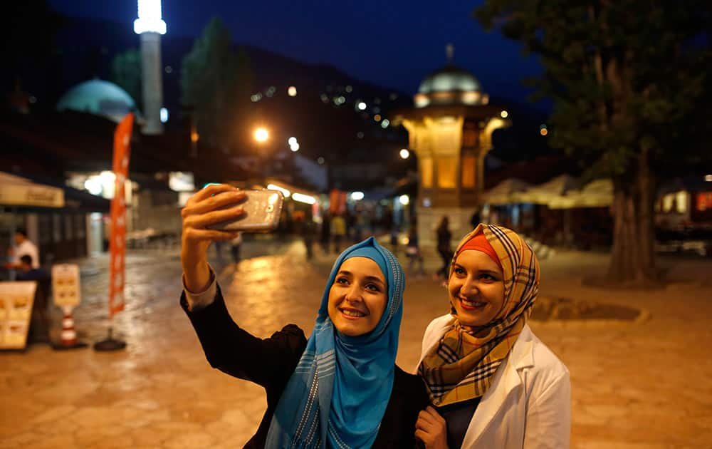Bosnian Muslim girls walk in the old part of Sarajevo on the first day of the fasting month of Ramadan, in Sarajevo, Bosnia.