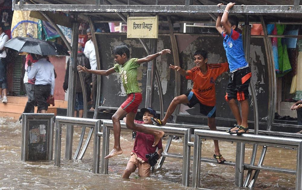 Children enjoying at a water logged road as it rains in Mumbai.