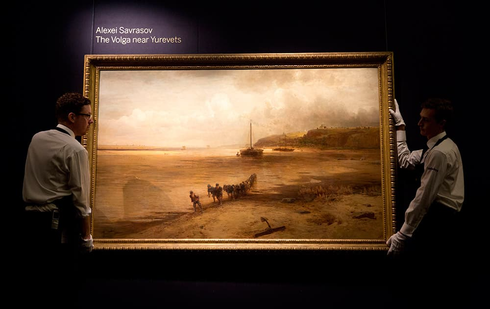 Sotheby's workers pose for photographs with the Alexei Savrasov oil on canvas entitled 'The Volga near Yurevets' at premises of the auction house in London.