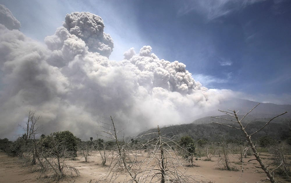 Mount Sinabung releases pyroclastic flows as seen from a coffee plantation affected by the volcano's previous eruption in Sigarang Garang, North Sumatra, Indonesia.