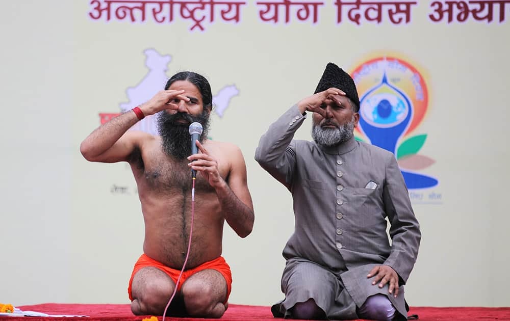 Yoga guru Baba Ramdev and former All India Imams Organisation general secretary and now a former member of the India Against Corruption core committee Mufti Shamoon Qasmi perform Anulom Vilom or Alternate Nostril Breathing exercises during a practice session ahead of International Day of Yoga in New Delhi.