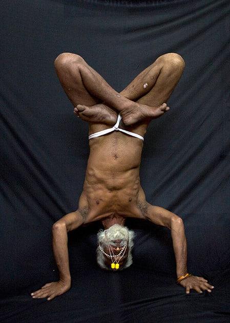 Hindu holy man, illustrates the yoga pose Ardha Sirasana, where the yogi lies on his back and puts his crossed legs in the air, in Guwahati.