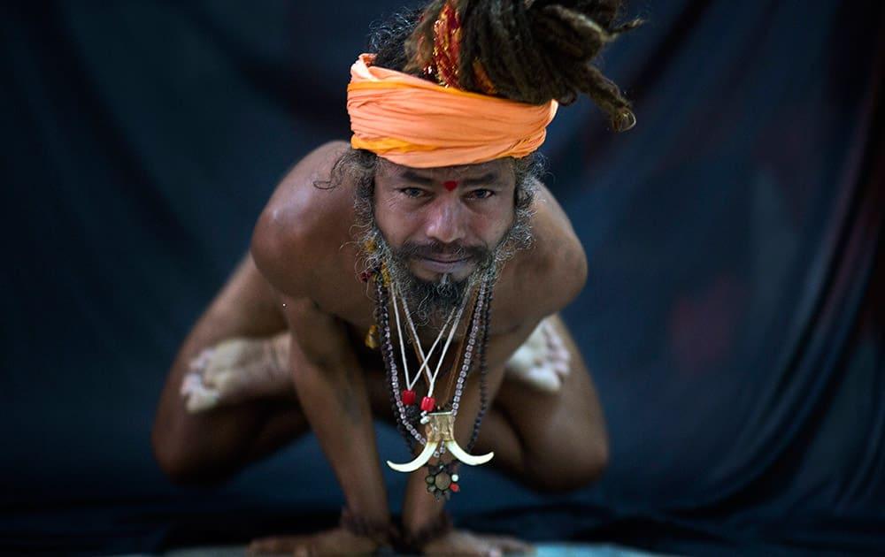 Hindu holy man, illustrates the yoga pose Kakasana, or the crow pose in Guwahati.