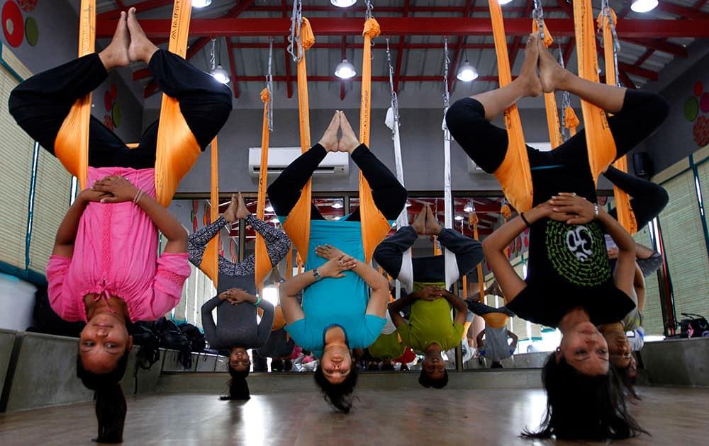 People perform anti gravity aerial yoga in Ahmadabad.
