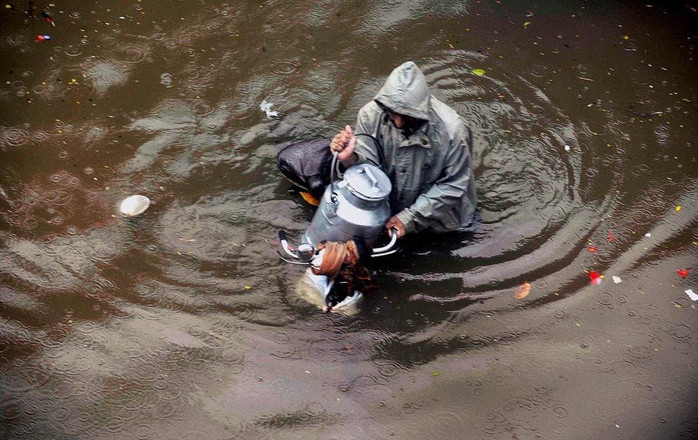 A milkman wades through a water logged road after heavy rains near Dadar in Mumbai.