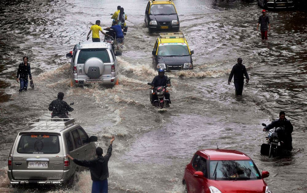 People wade through a water logged road after heavy rains near Dadar in Mumbai.