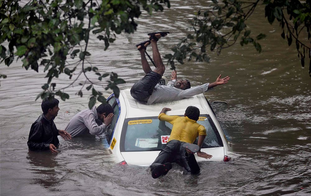 A vehicle stuck in rain water at a road as boys having fun after heavy shower in Mumbai.