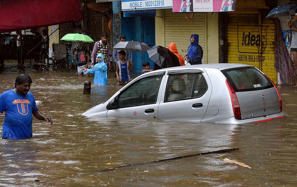 People wade through a water logged road after heavy rains in Mumbai.