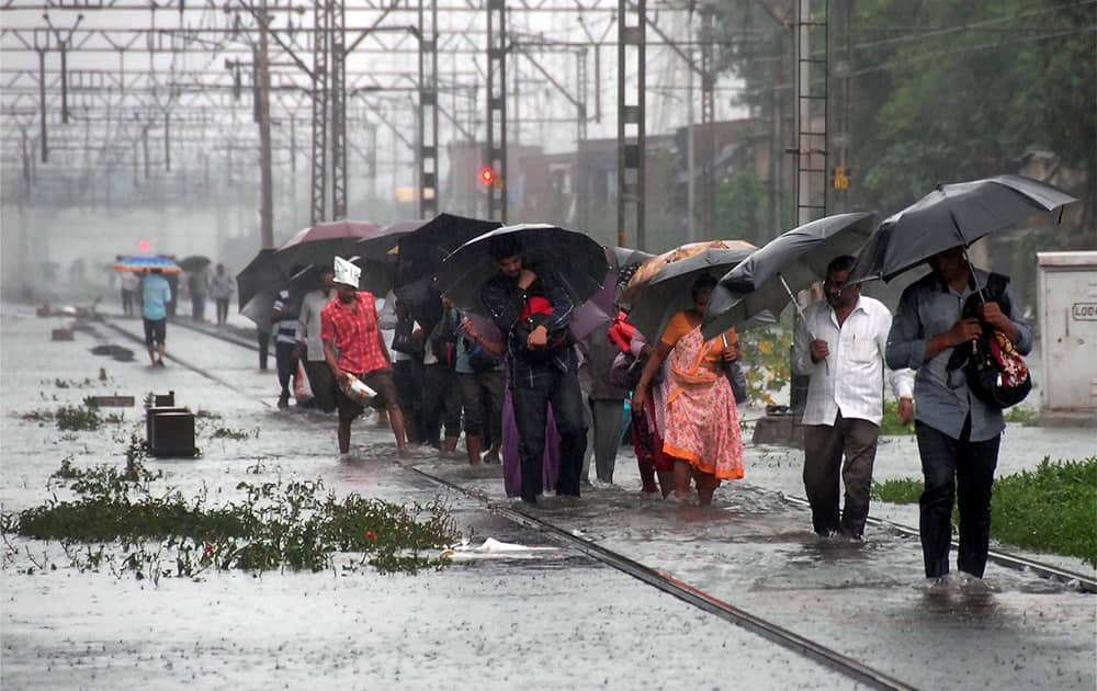 People walk through flooded railway tracks after heavy rains in Mumbai.