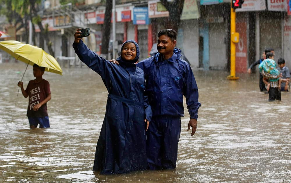 Couple take a selfie on a water-logged street as it rains in Mumbai.