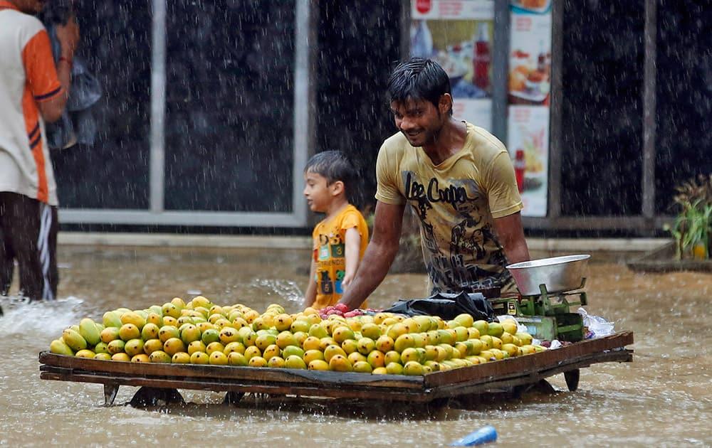 A fruit vendor pushes his cart through a flooded street during monsoon rains in Mumbai.