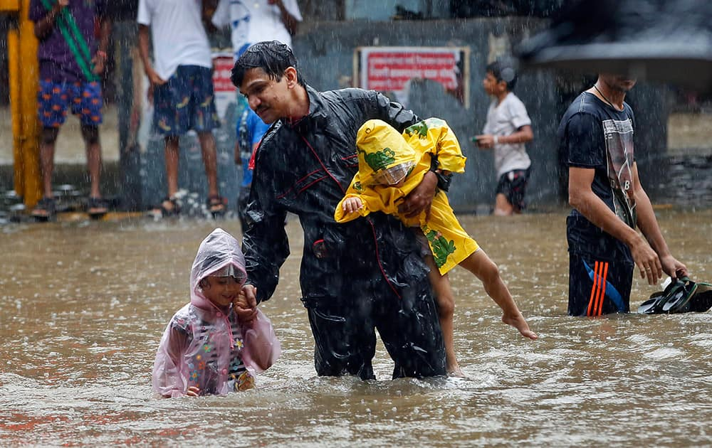 A man carries children and crosses a waterlogged street as it rains in Mumbai.