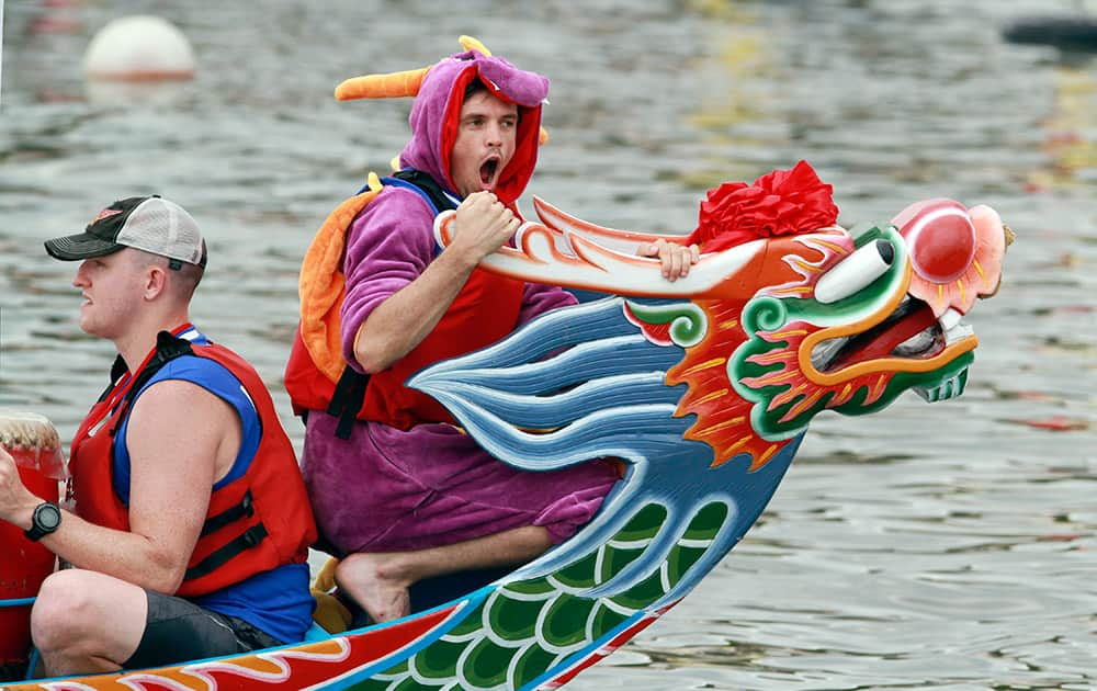 A boat captain wears a dragon costume during a traditional Chinese Dragon Boat race in Taipei, Taiwan.