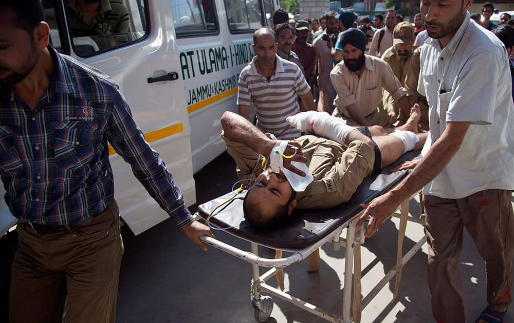 Kashmiri Muslims carry a wounded policeman on a stretcher outside a local hospital in Srinagar. A Pakistani prisoner was killed and five policemen sustained injuries in a suspected blast that took place inside a police vehicle.