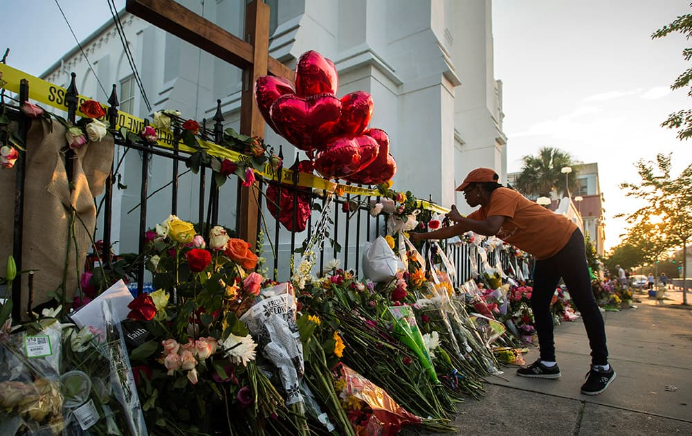 A mourner places flowers along the fence outside the Emanuel AME Church in Charleston, S.C.