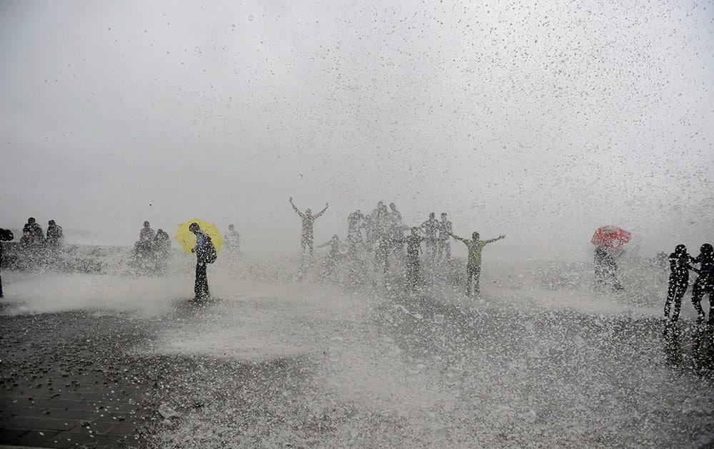 People enjoy high tide during monsoon season in Mumbai.