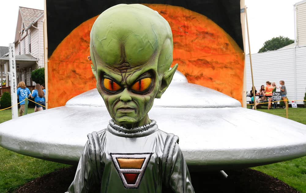 A figure representing a green alien is positioned in front of the permanent flying saucer replica in Mars, Pa. The small western Pennsylvania town has NASA joining in with a weekend celebration of the Northern Hemisphere Spring Equinox on the planet Mars, marking the start of a new year on the red planet which lasts about 687 Earth days.