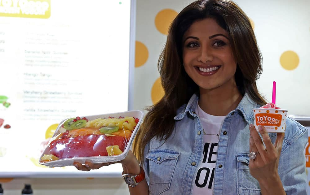 Bollywood actress Shilpa Shetty Kundra poses for a photograph with a frozen yogurt during its store launch in Bengaluru.